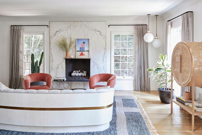 """<div class=""""caption""""> """"I love this couch because even though it seems modern it also reminds me of the '70. I think my next house will be like all '70, really funky,"""" says Duff. (The couch is a custom design by <a href=""""https://www.bespokefurniture.com/"""" rel=""""nofollow noopener"""" target=""""_blank"""" data-ylk=""""slk:Bespoke Furniture"""" class=""""link rapid-noclick-resp"""">Bespoke Furniture</a>.) """"I thought this would be the one room that would be for adults, but my kids freakin' love hanging out in there. But I don't mind; that's what makes a happy home."""" A pair of <a href=""""https://www.kellywearstler.com/"""" rel=""""nofollow noopener"""" target=""""_blank"""" data-ylk=""""slk:Kelly Wearstler"""" class=""""link rapid-noclick-resp"""">Kelly Wearstler</a> Laurel Lounge chairs, in montage and shell, are a treasured possession. """"I feel like I am going to have these until I am 98 years old, a grandma that's still going be sitting in those fantastic chairs."""" </div>"""