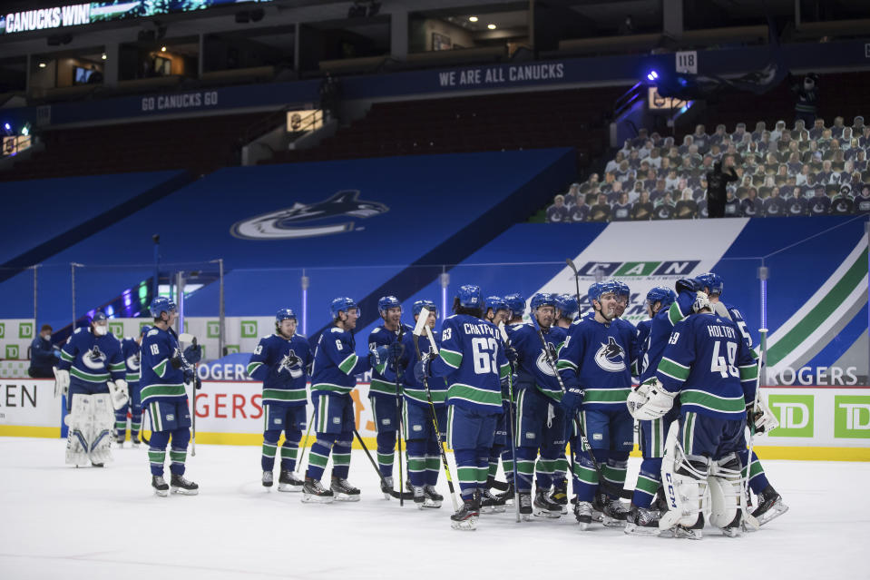 Vancouver Canucks goalie Braden Holtby, right, celebrates with his teammates after Vancouver defeated the Toronto Maple Leafs during an NHL hockey game in Vancouver, British Columbia, on Tuesday, April 20, 2021. (Darryl Dyck/The Canadian Press via AP)