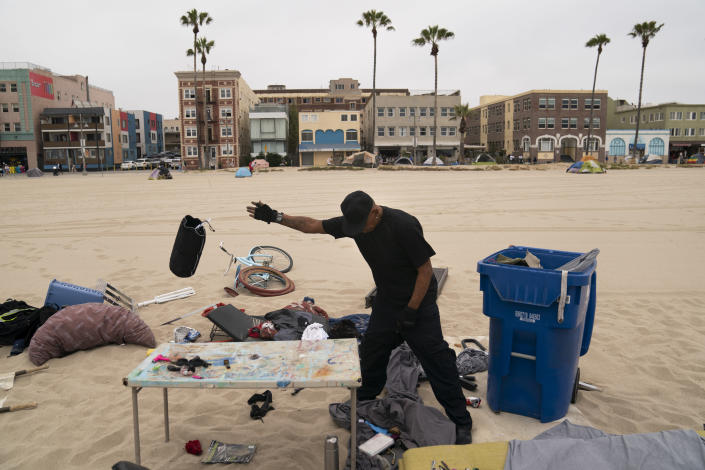 Donald Banks Jr. tosses a bag while sorting through his belongings on the beach in the Venice neighborhood of Los Angeles, Tuesday, June 29, 2021. The proliferation of homeless encampments on Venice Beach has sparked an outcry from residents and created a political spat among Los Angeles leaders. Residents of the gritty bohemian neighborhood that is one of LA's top tourist destinations are frustrated and angry over government inaction that allowed the camps to blossom during the pandemic. (AP Photo/Jae C. Hong)
