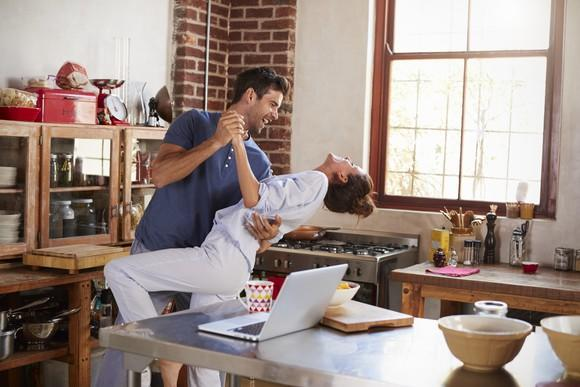 A smiling man and woman dancing in their kitchen
