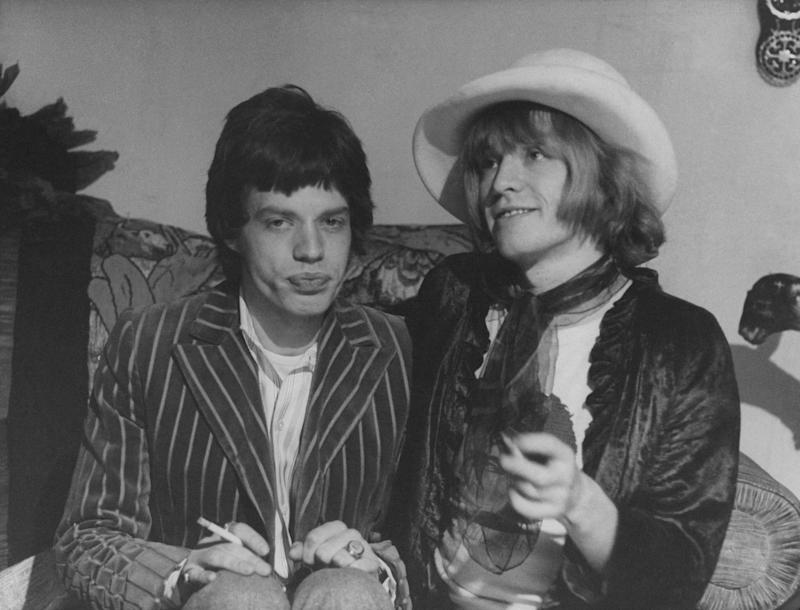 British singer and musician Mick Jagger (Michael Phillip Jagger) sitting beside British guitarist and multi-instrumentalist Brian Jones. The two are founding members of British band The Rolling Stones. 1967 (Photo by Mondadori Portfolio via Getty Images)