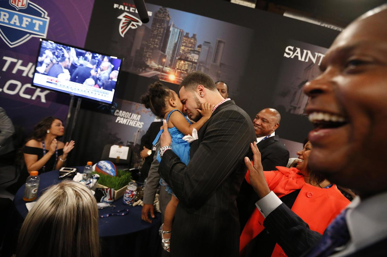 Mike Evans, from Texas A&M, holds his 2-year-old daughter Mackenzie as he reacts after being selected seventh overall by the Tampa Bay Buccaneers in the first round of the NFL football draft, Thursday, May 8, 2014, at Radio City Music Hall in New York. (AP Photo/Jason DeCrow)