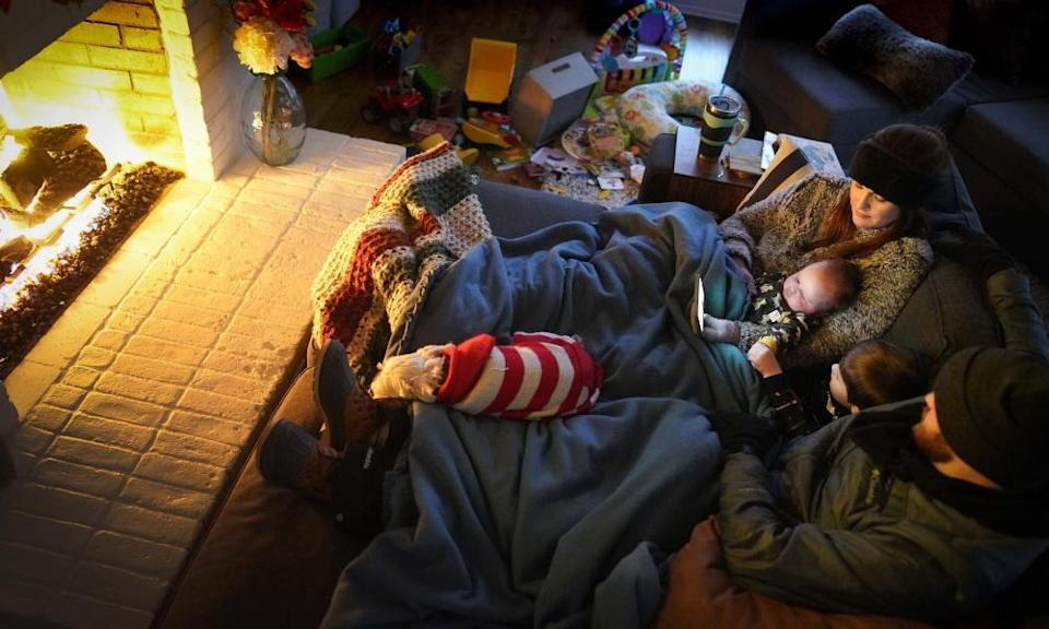 Dan Bryant and his wife Anna huddle by the fire with sons Benny, three, and Sam, 12 weeks, along with their dog, Joey, also wearing two doggie sweaters, with power out and temperatures dropping inside their home after a storm brought snow and freezing temperatures to Texas.
