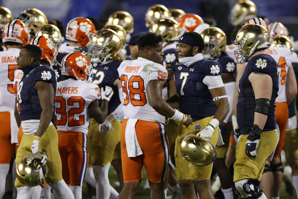 CHARLOTTE, NORTH CAROLINA - DECEMBER 19: Clemson Tigers players greet Notre Dame Fighting Irish players after the ACC Championship game at Bank of America Stadium on December 19, 2020 in Charlotte, North Carolina. The Clemson Tigers defeated the Notre Dame Fighting Irish 34-10. (Photo by Jared C. Tilton/Getty Images)