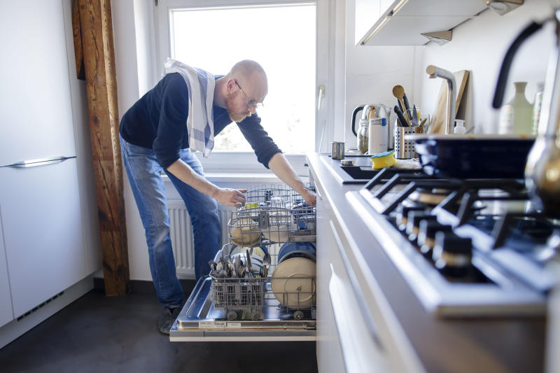 BERLIN, GERMANY - MARCH 26: Symbol photo on the subject of housework: A man puts away a dishwasher on March 26, 2020 in Berlin, Germany. (Photo by Thomas Trutschel/Photothek via Getty Images)