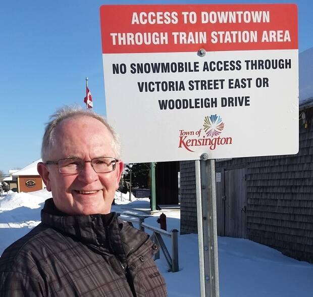 Kensington Mayor Rowan Caseley stands by the sign that tells snowmobilers where they can safely travel in the town.