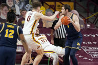Minnesota's Brandon Johnson (23) falls as he defends against Michigan's Hunter Dickinson (1) during the first half an NCAA college basketball game, Saturday, Jan. 16, 2021, in Minneapolis. (AP Photo/Jim Mone)
