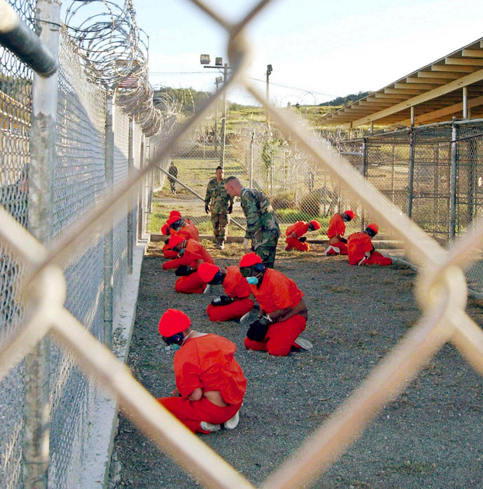 A file photo shows detainees sitting in a holding area watched by military police at Camp X-Ray inside Naval Base Guantanamo Bay, Cuba.  A file photo shows detainees sitting in a holding area watched by military police at Camp X-Ray inside Naval Base Guantanamo Bay, Cuba, during their processing into the temporary detention facility on January 11, 2002. Four remaining Britons and an Australian being held at Guantanamo Bay will be released soon, officials said on January 11, 2005, amid reports the number of prisoners at the U.S. military base would be radically reduced. EDITORIAL USE ONLY REUTERS/U.S. Department of Defense/Petty Officer 1st class Shane T. McCoy/Handout