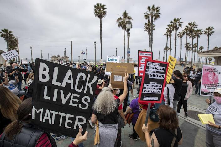 Protesters hold signs during a rally Sunday in Huntington Beach