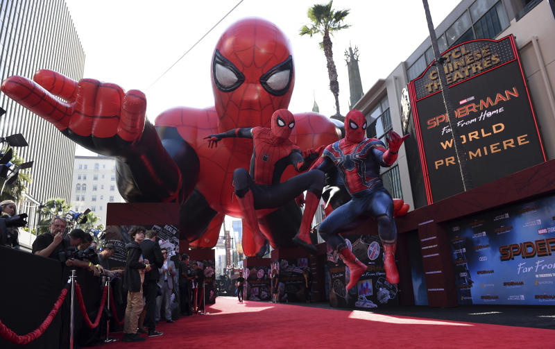 """Two Spider-Man characters jump in front of a Spider-Man float at the world premiere of """"Spider-Man: Far From Home"""" on Wednesday, June 26, 2019, at the TCL Chinese Theatre in Los Angeles. (Photo by Chris Pizzello/Invision/AP)"""
