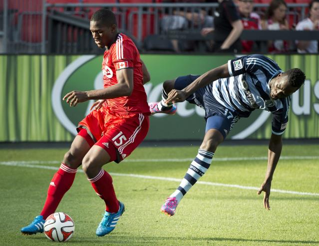 Toronto FC defender Doneil Henry, left, vies for the ball against Sporting Kansas City forward C.J. Sapong during the first half of an MLS soccer game Saturday, July 26, 2014, in Toronto. (AP Photo/The Canadian Press, Nathan Denette)