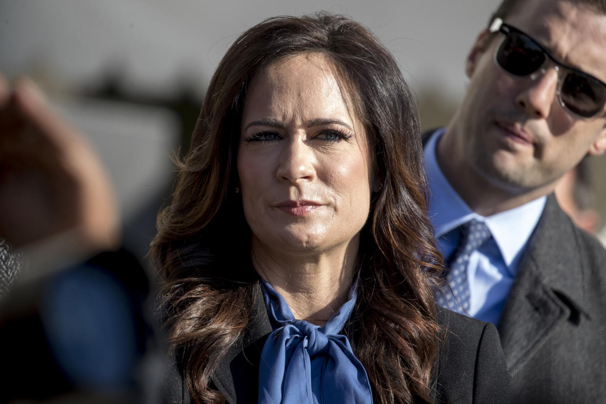 White House press secretary Stephanie Grisham listens as President Donald Trump speaks to reporters on the South Lawn of the White House in Washington, Friday, Nov. 8, 2019, before boarding Marine One for a short trip to Andrews Air Force Base, Md. and then on to Georgia to meet with supporters. (AP Photo/Andrew Harnik)