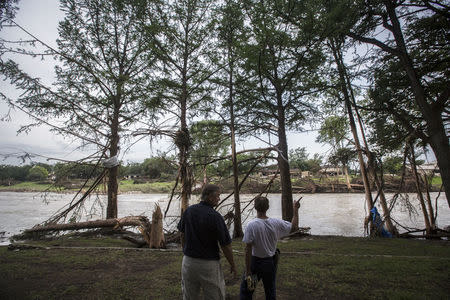 Burns Cleland (L) and Robert Wells (R) survey the flood damage done to the area surrounding the Blanco River in Wimberley, Texas May 26, 2015. REUTERS/Tamir Kalifa