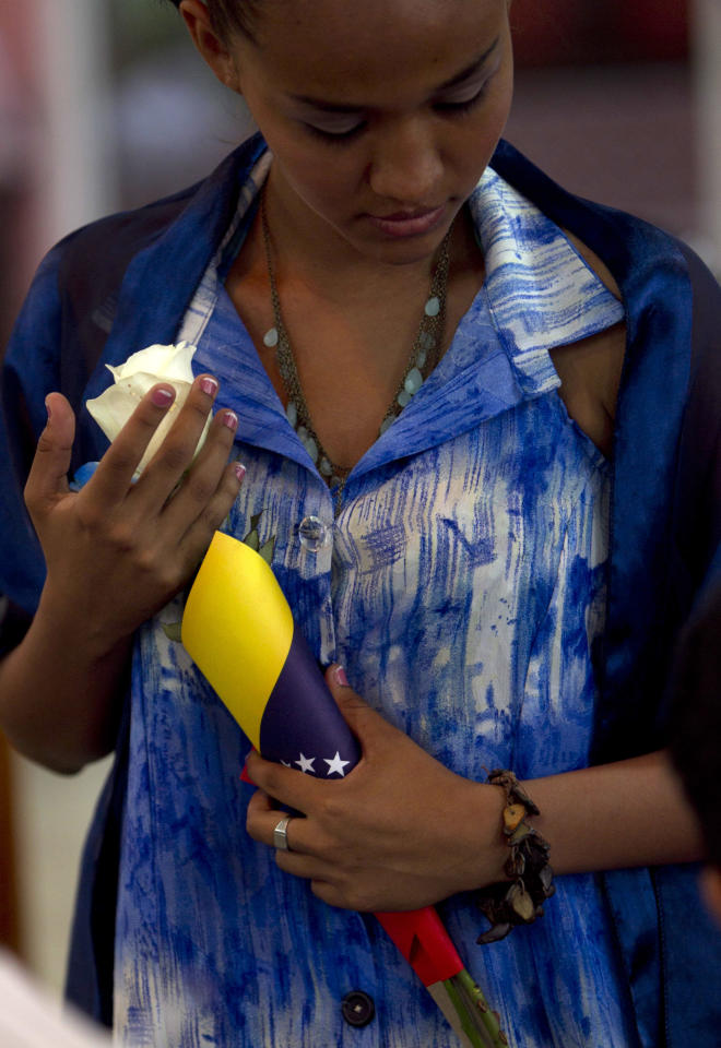 A woman holds a flower wrapped in a Venezuelan flag during mass in support of Venezuela's President Hugo Chavez in Managua, Nicaragua, Thursday March, 1, 2012. Doctors successfully extracted a tumor from Chavez's pelvic region and he was stable and recovering in Cuba on Tuesday with family at his side, Venezuela's Vice President Elias Jaua said. (AP Photo/Esteban Felix)