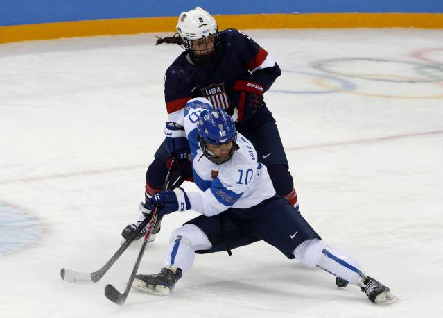 Megan Bozek (9) of the U.S. battles with Finland's Linda Valimaki (front) during the first period of their women's preliminary round hockey game at the Sochi 2014 Winter Olympic Games February 8, 2014. REUTERS/Grigory Dukor (RUSSIA - Tags: SPORT OLYMPICS ICE HOCKEY)