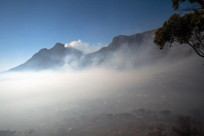 Smoke engulfs the city of Cape Town, South Africa, Tuesday April 20, 2021. A massive fire spreading on the slopes of the city's famed Table Mountain, at right, is kept under control as firemen and helicopters take advantage of the low winds to contain the blaze. (AP Photo/Jerome Delay)