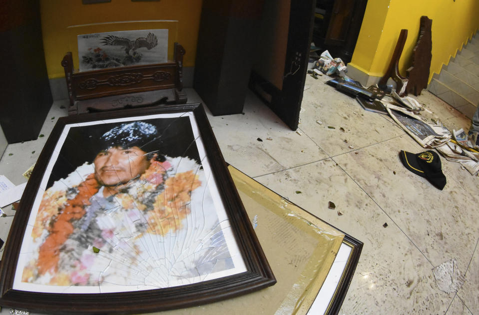 A broken portrait of former Bolivia's President Evo Morales is on the floor of his private home in Cochabamba, Bolivia, after hooded opponents broke into the residence on Sunday, Nov. 10, 2019. Morales resigned Sunday under mounting pressure from the military and the public after his re-election victory triggered weeks of fraud allegations and deadly protests. (AP Photo)