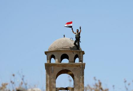 FILE PHOTO: A Syrian army soldier gestures as he holds a Syrian flag in Quneitra.