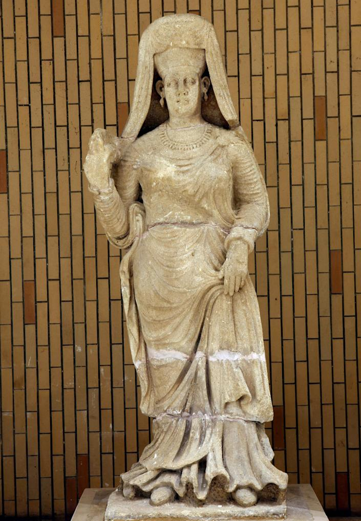 In this Wednesday, April 3, 2013 photo, a limestone statue of a woman dressed with a cloak, found at Hatra is displayed at the Iraqi National Museum in Baghdad, Iraq. Ten years after Iraq's national museum was looted and smashed by frenzied thieves during the U.S.-led invasion in 2003 to topple Saddam Hussein, it's still far from ready for a public re-opening. Work to overcome decades of neglect and the destruction of war has been hindered by power struggles, poorly-skilled staff and the persistent violence plaguing the country, said Bahaa Mayah, Iraq's most senior antiquities official. (AP Photo/Hadi Mizban)