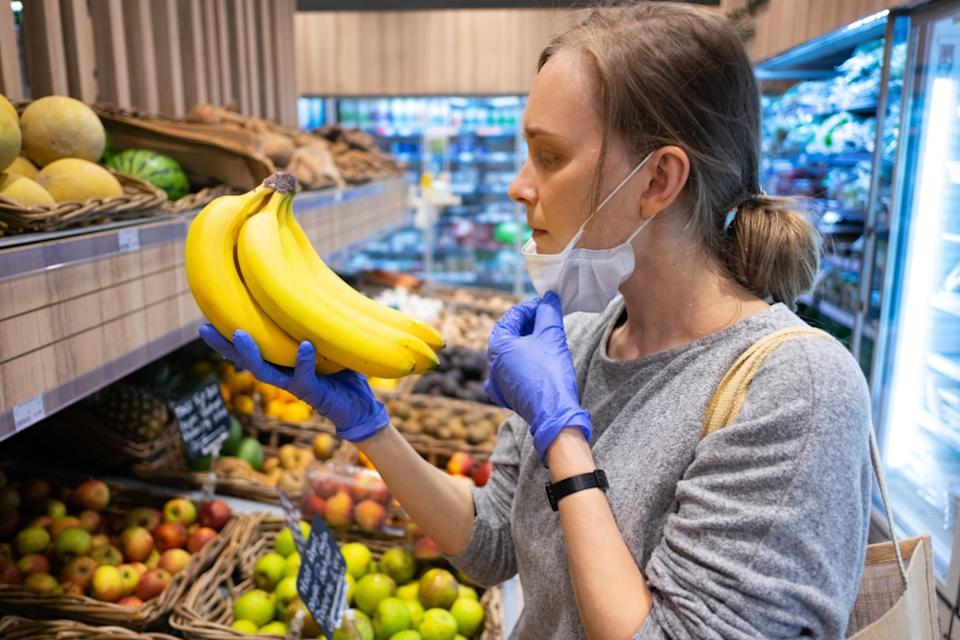 Focused woman taking off face mask while choosing fruits in grocery store.