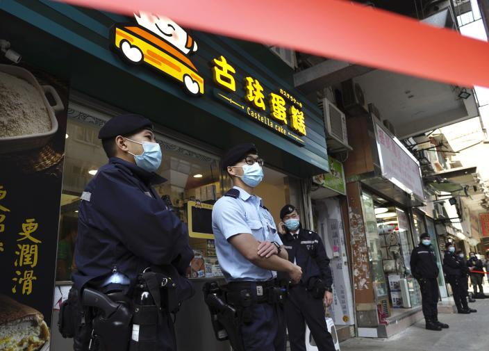 Police officers stand guard outside office of District councillor and lawyer Daniel Wong Kwok-tung, while police searching in Hong Kong, Thursday, Jan. 14, 2021. Wong, a member of the city's Democratic Party, is known for providing legal assistance to hundreds of protesters arrested during the anti-government protests in Hong Kong in 2019. Hong Kong national security police on Thursday arrested a lawyer and 10 others on suspicion of helping 12 Hong Kongers try to flee the city, local media reported in the latest arrests in an ongoing crackdown on dissent. (AP Photo/Vincent Yu)