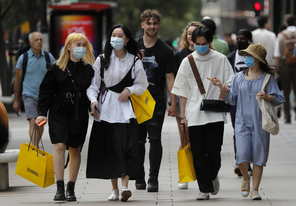 Shoppers wear face coverings to protect themselves from COVID-19 as they walk along Oxford Street in London, Friday, July 24, 2020. New rules on wearing masks in England have come into force, with people going to shops, banks and supermarkets now required to wear face coverings. Police can hand out fines of 100 pounds ($127) if people refuse, but authorities are hoping that peer pressure will prompt compliance. (AP Photo/Frank Augstein)