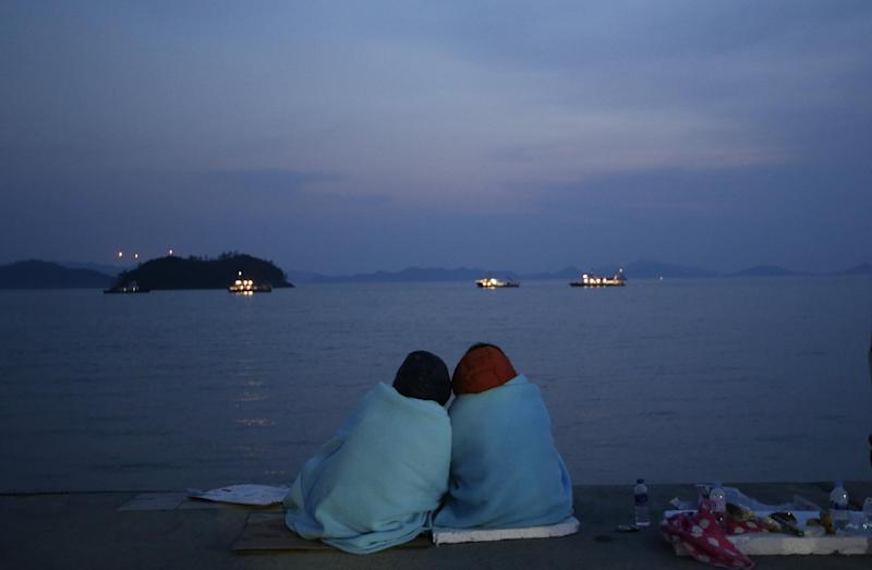 Relatives of passengers aboard the sunken ferry Sewol sit near the sea at a port in Jindo, south of Seoul, South Korea, Sunday, April 20, 2014. After more than three days of frustration and failure, divers on Sunday finally found a way into the submerged ferry off South Korea's southern shore, discovering more than a dozen bodies inside the ship and pushing the confirmed death toll to over four dozens, officials said. (AP Photo/Lee Jin-man)