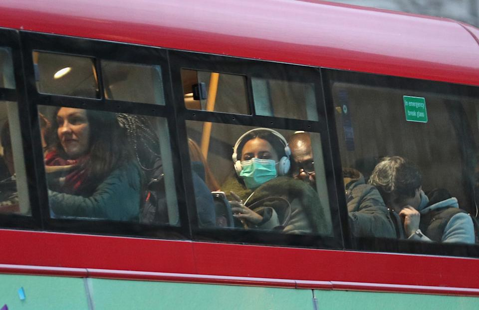 A woman wearing a face mask on a bus in London, as the first case of coronavirus has been confirmed in Wales and two more were identified in England - bringing the total number in the UK to 19.