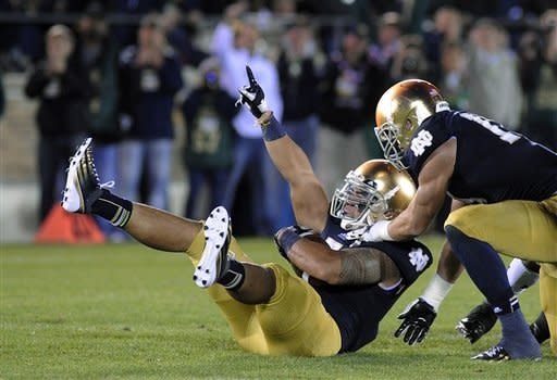 Notre Dame's Manti Te'o, left, reacts with Zeke Motta after Te'o makes an interception during the first half of an NCAA college football game against Michigan Saturday, Sept. 22, 2012, in South Bend, Ind. (AP Photo/Joe Raymond)