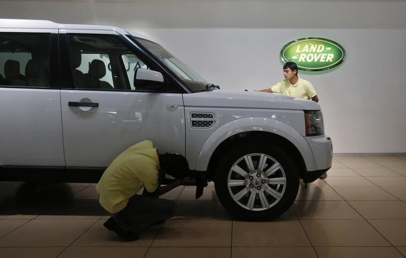 Showroom attendants polish a Land Rover vehicle at a Jaguar Land Rover showroom in Mumbai