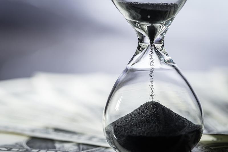 An hourglass with black sand sits on some dollar bills.