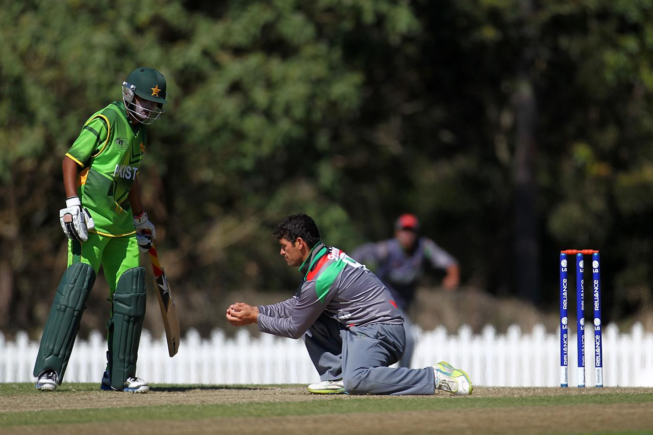 SUNSHINE COAST, AUSTRALIA - AUGUST 11:  Shabir Ahmed of Afghanistan (C) catches out Imam-ul-Haq of Pakistan from his own bowling during the ICC U19 Cricket World Cup 2012 match between Pakistan and Afghanistan at John Blanck Oval on August 11, 2012 in Sunshine Coast, Australia.  (Photo by Graham Denholm-ICC/Getty Images)