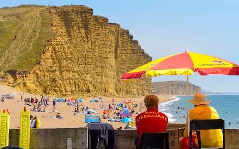 RNLI Lifeguards keeping watch over the sunbathers on the beach enjoying the hot sunshine at the seaside resort of West Bay in Dorset - Credit: Graham Hunt/Alamy Live News