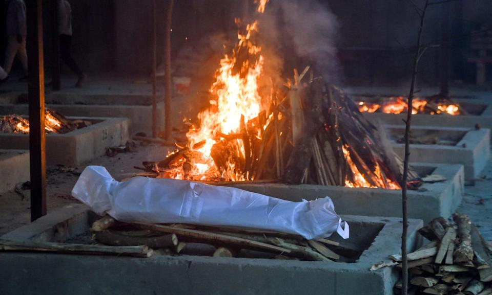 A person who died of Covid-19 is laid on a pyre at Sarai Kale Khan crematorium on May 6, 2021 in New Delhi, India. Source: Getty