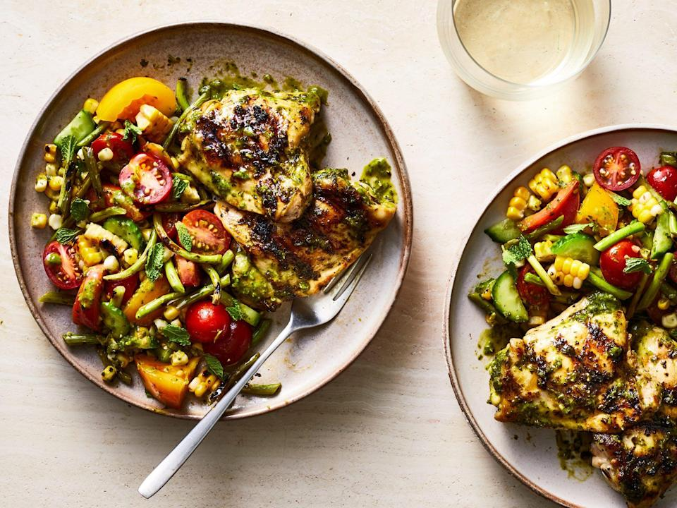 """<p>This grilled scape salad is crisp, light, and refreshing-in other words, it tastes like summertime. Tomatoes, corn, cucumber, and other summer veggies covered in lemon-parsley dressing and fresh mint perfectly combine with a charred, juicy chicken thigh. <a href=""""https://www.myrecipes.com/how-to/cooking-questions/difference-between-garlics"""" rel=""""nofollow noopener"""" target=""""_blank"""" data-ylk=""""slk:Garlic"""" class=""""link rapid-noclick-resp"""">Garlic</a> scapes are in season in late spring and early summer. If you can't find them at your local farmers' market or produce stand, try an international grocery. Round everything out with a crusty loaf of bread and a glass of white wine. </p>"""