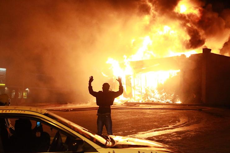 """A protestor poses for a """"hands up"""" photo in front of a burning building on West Florissant Ave. in Ferguson, Mo., Monday, Nov. 24, 2014. (AP Photo/St. Louis Post-Dispatch, Christian Gooden) Click for slideshow"""