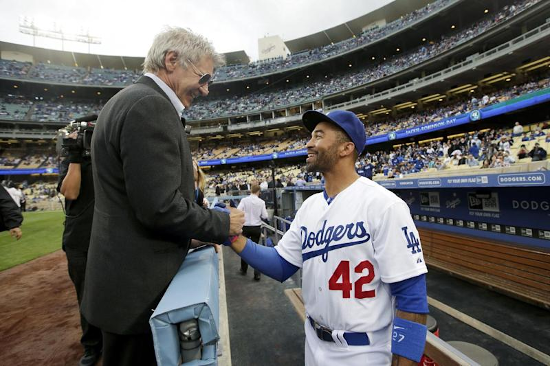 Actor Harrison Ford, left, shakes hands with Los Angeles Dodgers' Matt Kemp during a Jackie Robinson Day ceremony before a baseball game against the San Diego Padres in Los Angeles, Monday, April 15, 2013. (AP Photo/Jae C. Hong)