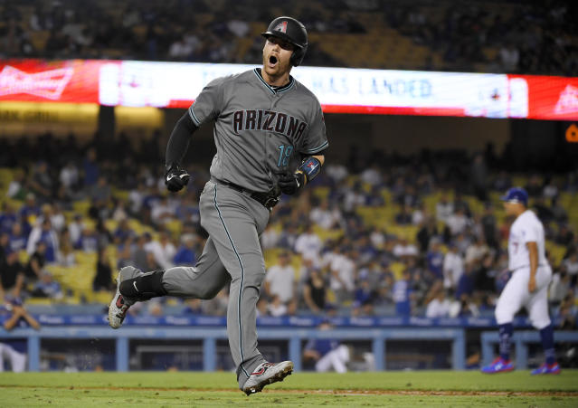 Arizona Diamondbacks' Carson Kelly, left, celebrates toward his dugout as he runs to first after hitting a solo home run off of Los Angeles Dodgers relief pitcher Julio Urias, right, during the 11th inning of a baseball game Friday, Aug. 9, 2019, in Los Angeles. (AP Photo/Mark J. Terrill)