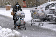 A shopper pushes a full grocery cart through heavy snow in a parking lot, Saturday, Dec. 5, 2020, in Marlborough, Mass. The northeastern United States is seeing the first big snowstorm of the season. (AP Photo/Bill Sikes)