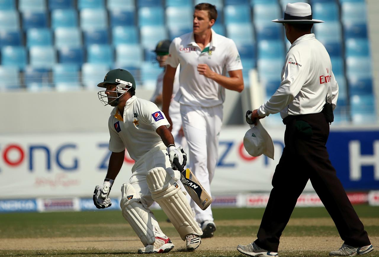 Batsman Asad Shafiq (C-L) of Paskistan runs between the wickets as bowler Morne Morkel of South Africa is seen in the background during the fourth day of the second Test cricket match between Pakistan and South Africa in Dubai on October 26, 2013. AFP PHOTO/MARWAN NAAMANI        (Photo credit should read MARWAN NAAMANI/AFP/Getty Images)