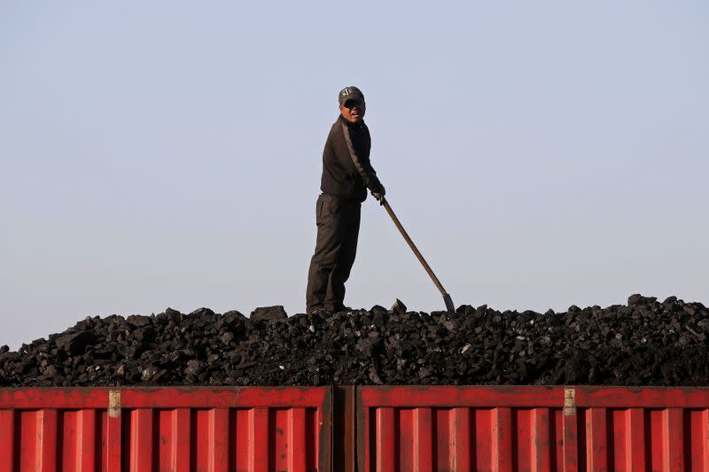 A worker speaks as he loads coal on a truck at a depot near a coal mine from the state-owned Longmay Group on the outskirts of Jixi, Heilongjiang, China