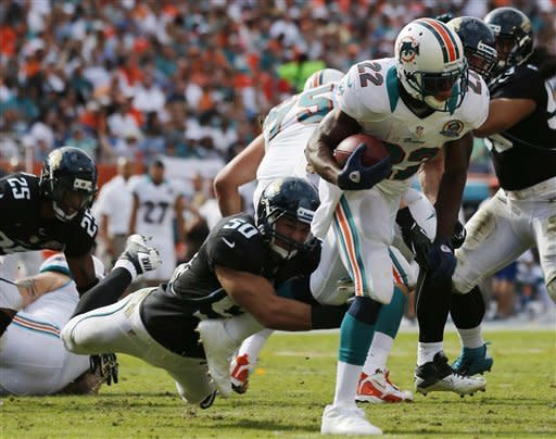 Miami Dolphins running back Reggie Bush (22) runs as Jacksonville Jaguars outside linebacker Russell Allen (50) holds on to his leg during the first half of an NFL football game on Sunday, Dec. 16, 2012, in Miami. (AP Photo/John Bazemore)