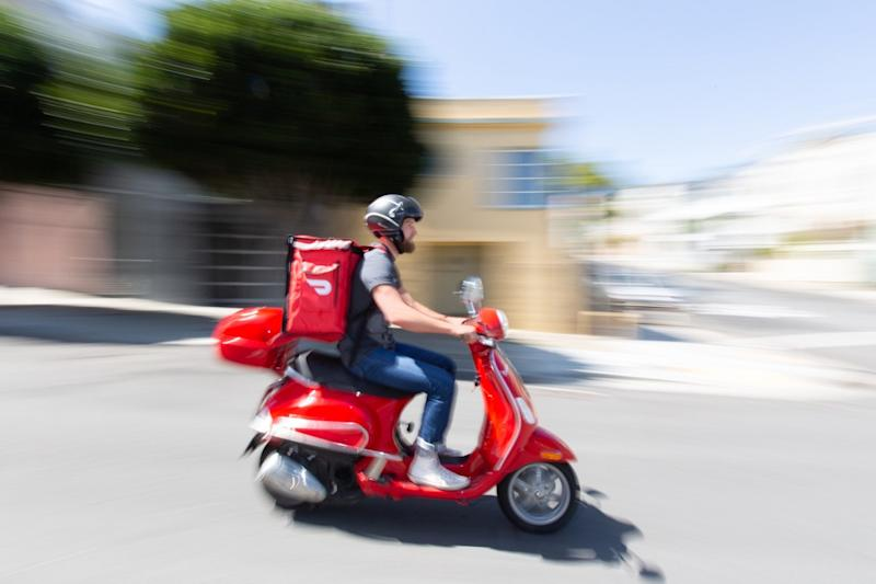 A DoorDash delivery person is seen riding a moped to deliver a product.