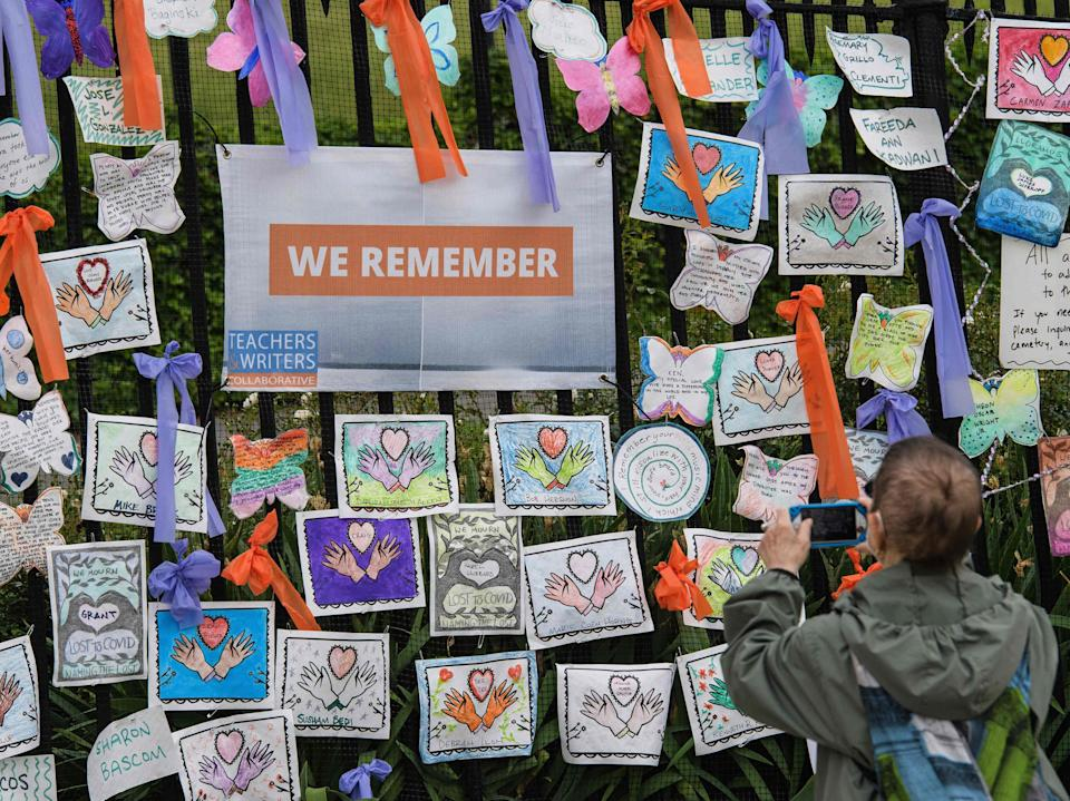 """A person takes a picture at the """"Naming the Lost Memorials"""" installation to remember the lives lost due to the coronavirus pandemic at The Green-Wood Cemetery on 11 June 2021 in New York City (AFP via Getty Images)"""