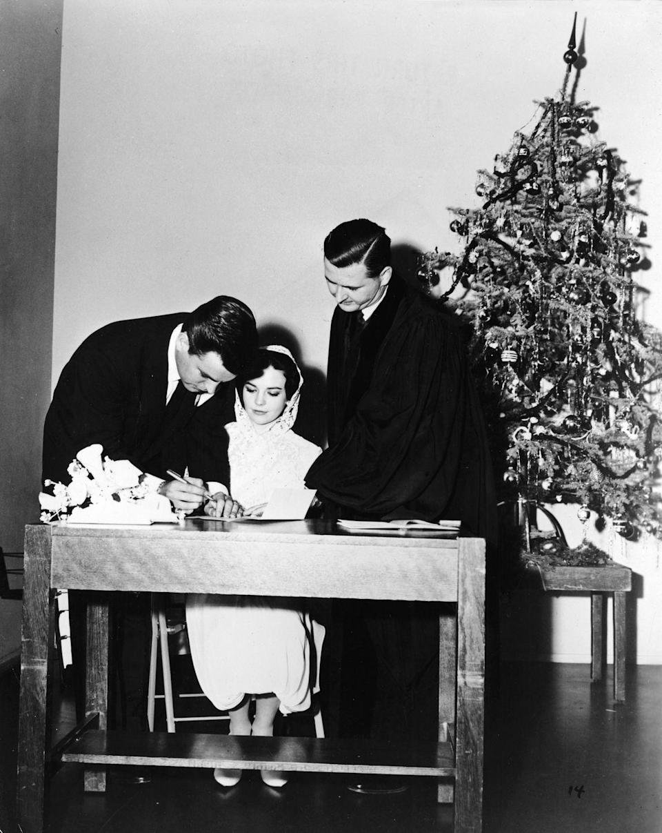 <p>The actors sign their marriage license while a judge looks on at a Scottsdale, Arizona courthouse on December 28, 1957.</p>