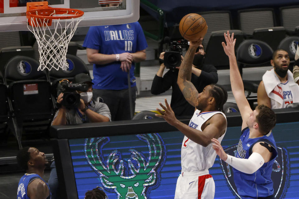 Los Angeles Clippers forward Kawhi Leonard (2) scores a basket as he is defended by Dallas Mavericks guard Luka Doncic, front right, in the first half during Game 6 of an NBA basketball first-round playoff series in Dallas, Friday, June 4, 2021. (AP Photo/Michael Ainsworth)