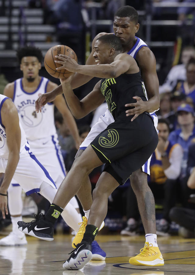 Atlanta Hawks guard Isaiah Taylor, foreground, is defended by Golden State Warriors forward Kevon Looney during the first half of an NBA basketball game in Oakland, Calif., Friday, March 23, 2018. (AP Photo/Jeff Chiu)