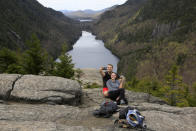 Sidney Gleason, right, and Joe Gorsuch, both of Syracuse, take a selfie with Lower Ausable Lake in the background, while taking a break at Indian Head summit inside the Adirondack Mountain Reserve, Saturday, May 15, 2021, near St. Huberts, N.Y. A free reservation system went online recently to control growing number of visitors packing the parking lot and tramping on the trails through the private land of the Adirondack Mountain Reserve. The increasingly common requirements, in effect from Maui to Maine, offer a trade-off to visitors, sacrificing spontaneity and ease of access for benefits like guaranteed parking spots and more elbow room in the woods. (AP Photo/Julie Jacobson)