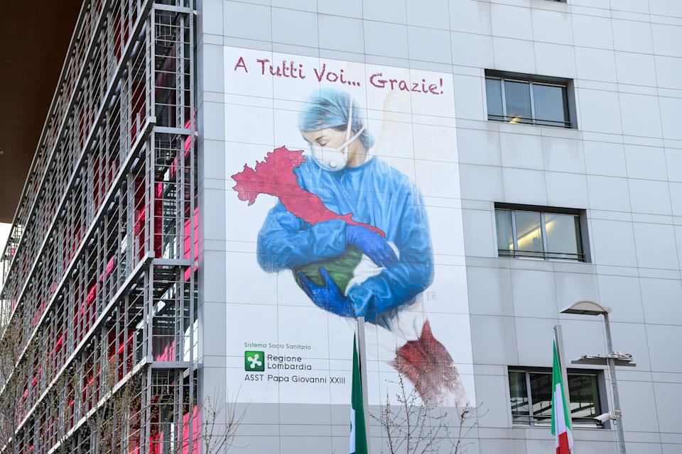 A mural by artist Franco Rivolli Art, depicting a nurse wearing a face mask, with wings behind her back and cradling Italy, is pictured on a wall of the Papa Giovanni XXIII Hospital in Bergamo, Lombardy, on March 16, 2020. (Photo by Piero Cruciatti / AFP) / RESTRICTED TO EDITORIAL USE - MANDATORY MENTION OF THE ARTIST UPON PUBLICATION - TO ILLUSTRATE THE EVENT AS SPECIFIED IN THE CAPTION (Photo by PIERO CRUCIATTI/AFP via Getty Images)