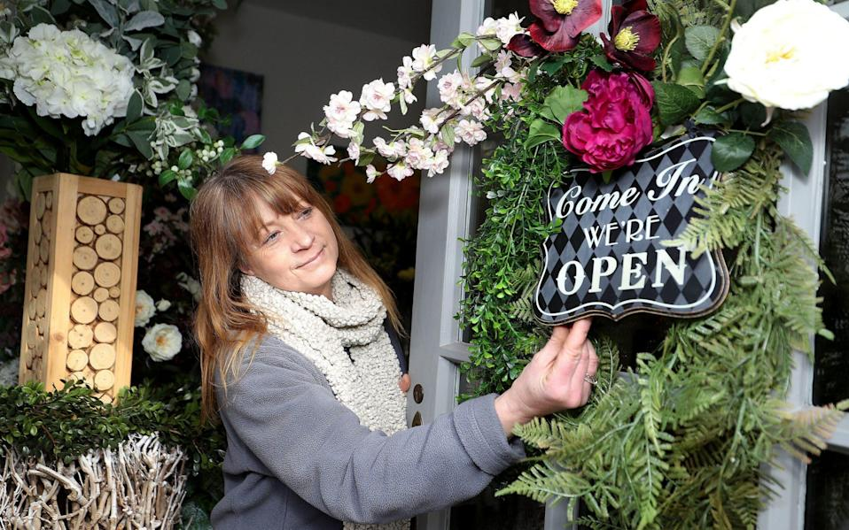Florist Jo Ashton, owner of The White Orchid in Knutsford, Cheshire, adjusts the open sign on her shop door as she prepares to welcome back customer - Martin Rickett/PA